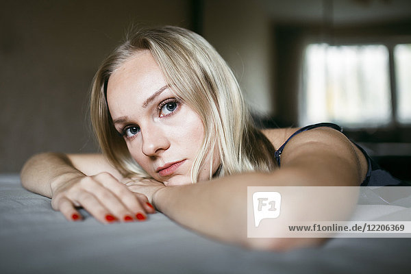 Close up of serious Caucasian woman resting on bed, Close up of serious Caucasian woman resting on bed