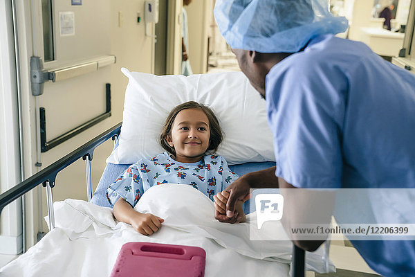 Doctor holding hand of girl in hospital bed