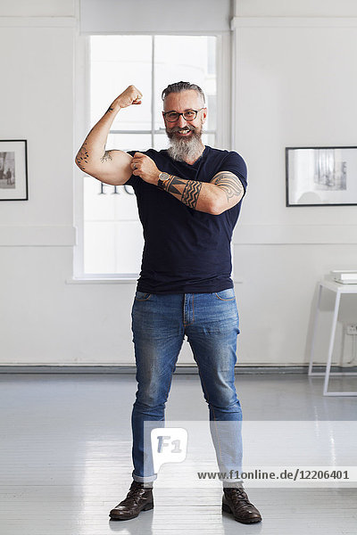 Smiling muscular Caucasian hipster man flexing biceps