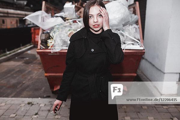 Caucasian woman wearing black coat smoking cigarette near dumpster