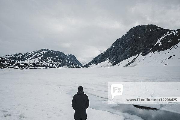 Caucasian man standing in mountain landscape in winter