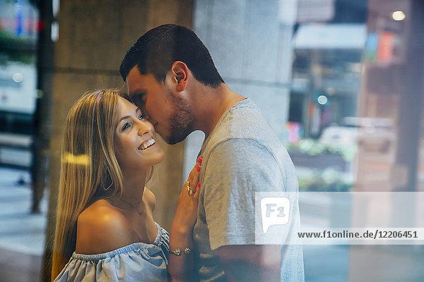 Caucasian man kissing woman on cheek behind window