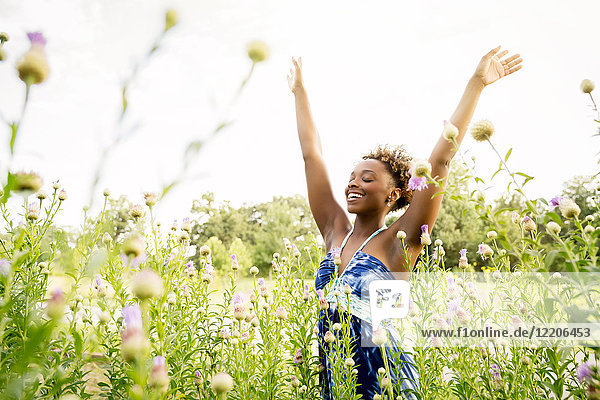 Smiling mixed race woman celebrating in field of wildflowers