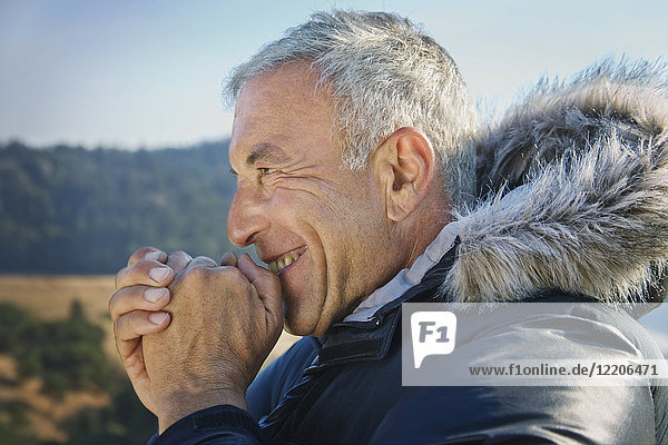 Smiling Caucasian man wearing coat with fur hood