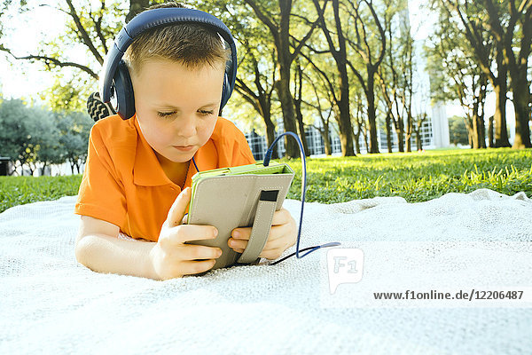 Serious Caucasian boy laying on blanket in park listening to digital tablet