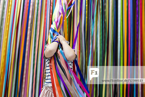 Caucasian girl playing with colorful hanging streamers