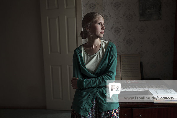 Portrait of pensive Caucasian woman leaning on piano