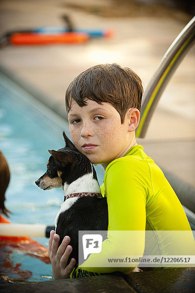 Caucasian boy in swimming pool holding dog