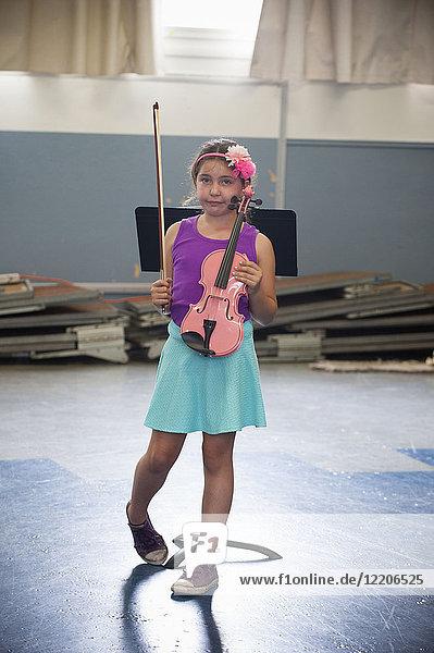 Portrait of awkward Hispanic girl holding pink violin