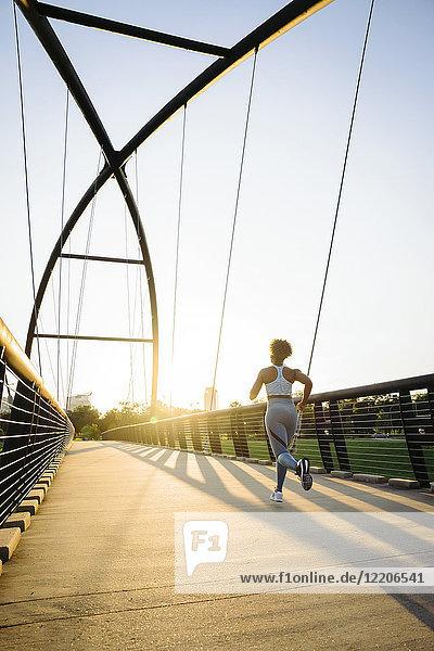 Distant mixed race woman running on bridge