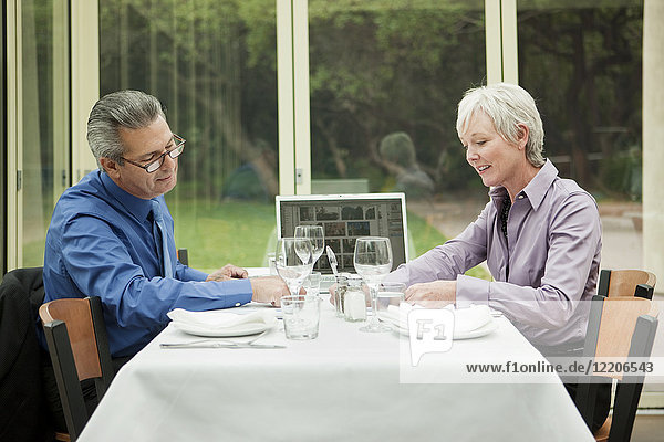 Business people with laptop working at table in restaurant