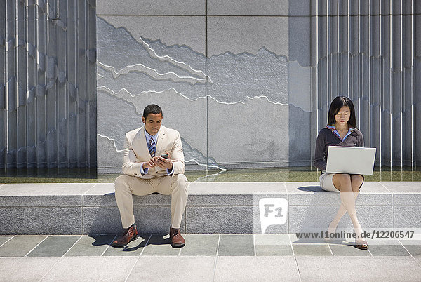 Business people sitting on concrete wall outdoors using technology