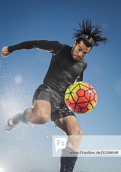 Water splashing on Hispanic man kicking soccer ball
