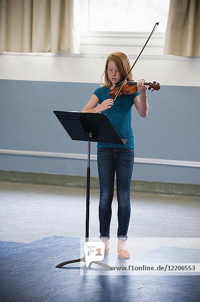Caucasian girl practicing violin