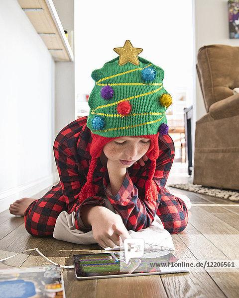 Caucasian boy wearing Christmas tree stocking-cap using digital tablet on floor