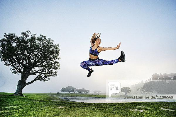 Mixed race woman exercising and jumping near lake
