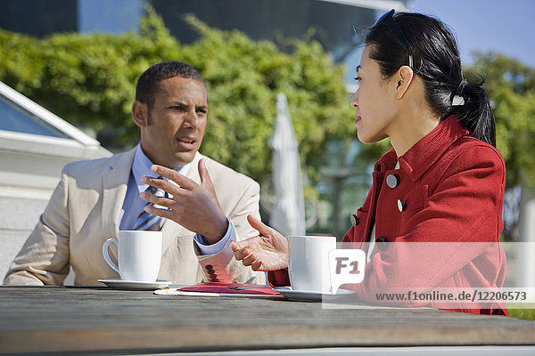 Business people talking and drinking coffee outdoors