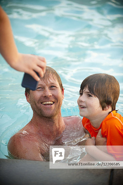 Hand holding cell phone for Caucasian father and son in swimming pool