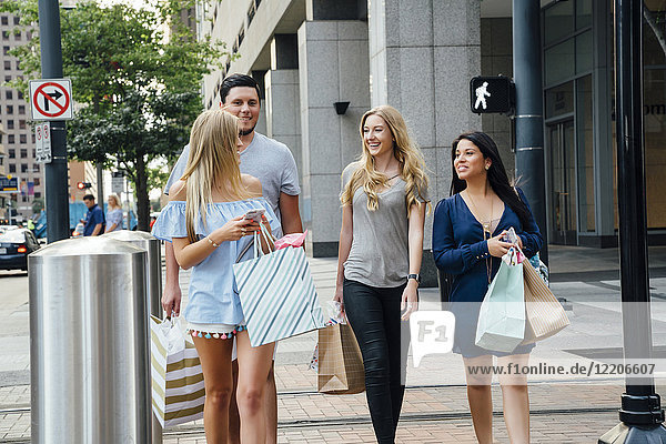 Friends walking in city carrying shopping bags texting on cell phones