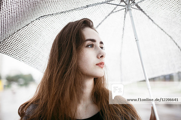 Caucasian woman holding white umbrella