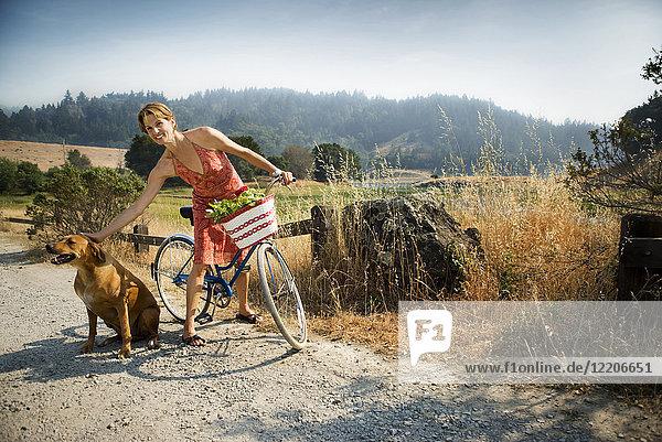 Smiling Hispanic woman standing with bicycle petting dog