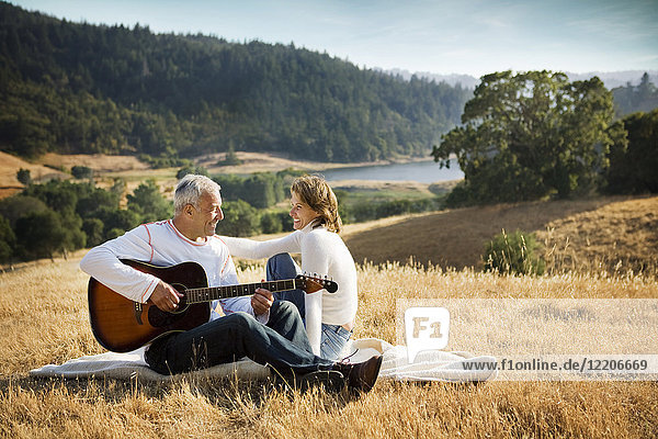 Man sitting on blanket in field playing guitar for woman