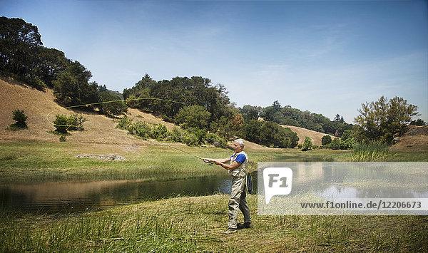 Caucasian man fishing at river