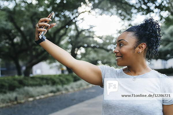 Smiling Black woman posing for cell phone selfie