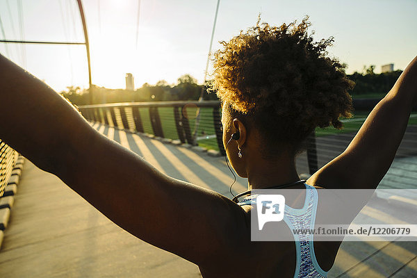 Mixed Race woman wearing earbuds stretching arms on bridge