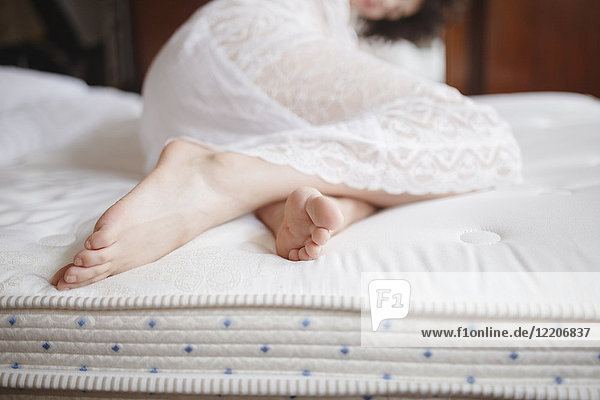 Feet of Caucasian woman laying on bed