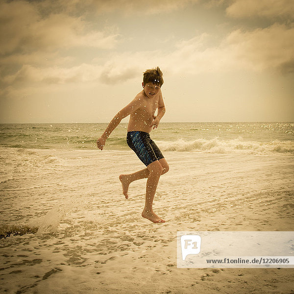 Caucasian boy jumping and splashing in ocean waves