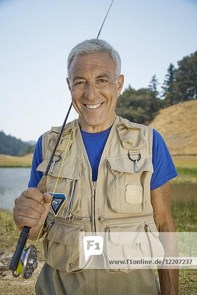 Portrait of smiling Caucasian man holding fishing rod