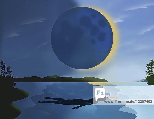 Frau schwimmt in einem See während der Sonnenfinsternis
