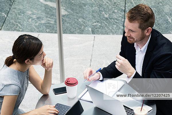 Junger Geschäftsmann und Frau mit Laptops treffen sich im Straßencafé