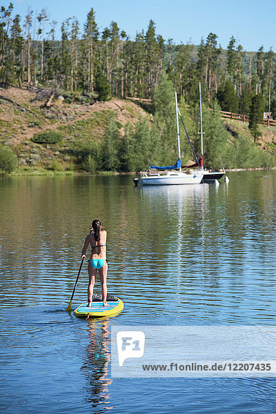 Rückansicht einer jungen Frau beim Paddelbootfahren im Stehen auf einem See  Frisco  Colorado  USA
