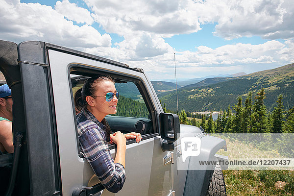 Young woman on road trip looking out from parked off road vehicle  Breckenridge  Colorado  USA