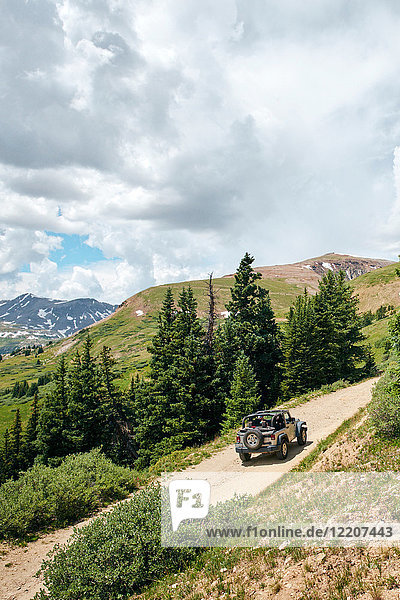 Road trip couple driving convertible off road vehicle on rural mountain road  Breckenridge  Colorado  USA