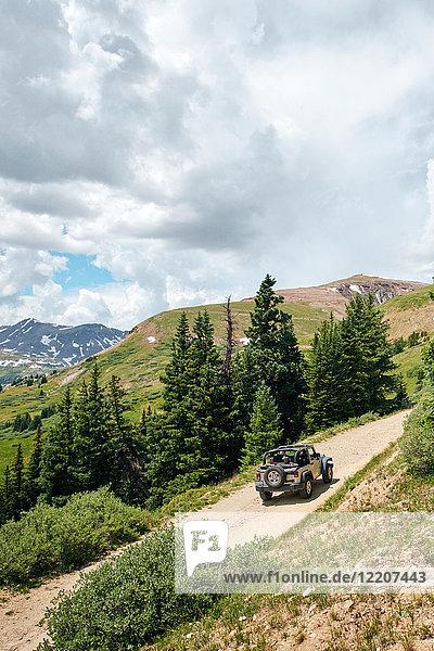 Roadtrip-Ehepaar fährt Cabrio-Geländewagen auf ländlicher Bergstraße  Breckenridge  Colorado  USA