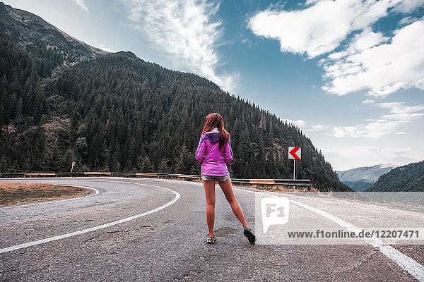 Junge Frau steht auf Bergstraße mit Haarnadelkurve  Draja  Vaslui  Rumänien  Rückansicht
