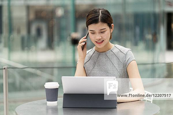 Junge Stadtgeschäftsfrau telefoniert mit Smartphone vom Straßencafé aus