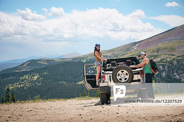 Road trip couple unpacking four wheel convertible in Rocky mountains  Breckenridge  Colorado  USA