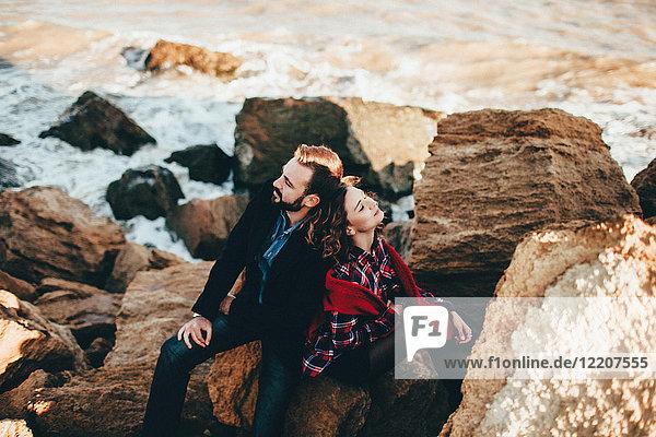 Romantisches Paar mittlerer Erwachsener  die Rücken an Rücken auf einem Strandfelsen sitzen  Oblast Odessa  Ukraine