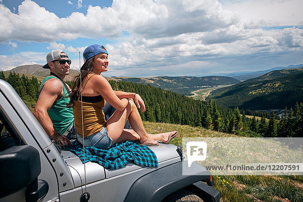 Road trip couple looking from car hood in Rocky Mountains  Breckenridge  Colorado  USA