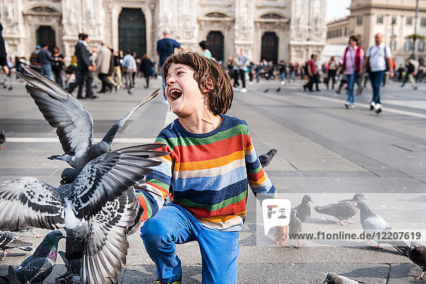 Boy laughing while feeding pigeons in square  Milan  Lombardy  Italy