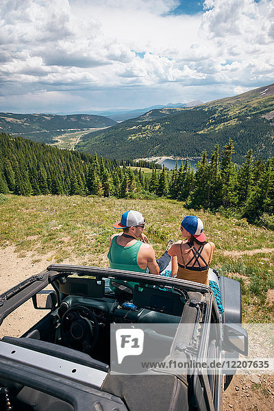 Rear view of road trip couple sitting on four wheel convertible hood in Rocky mountains  Breckenridge  Colorado  USA
