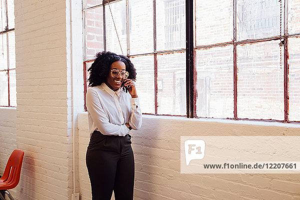 Frau in industriellem Bürogebäude telefoniert auf Smartphone