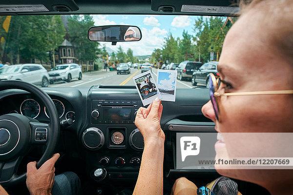 Nahaufnahme einer jungen Frau auf Autoreise mit Sofortbildaufnahme  Breckenridge  Colorado  USA