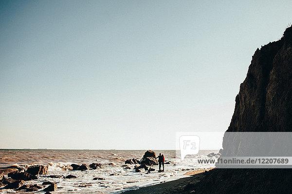Distanzansicht eines mittelgroßen erwachsenen Paares  das auf einem Felsen am Wasser am Strand steht  Oblast Odessa  Ukraine