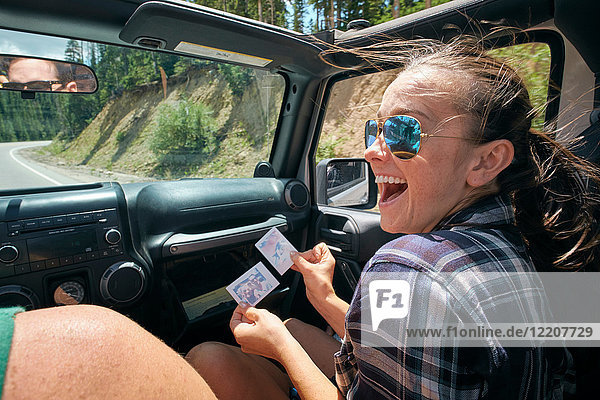 Young woman on road trip with boyfriend laughing at instant photograph  Breckenridge  Colorado  USA