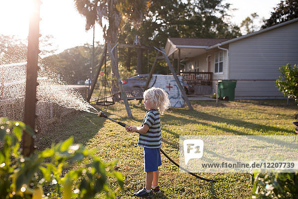 Boy spraying water from hosepipe